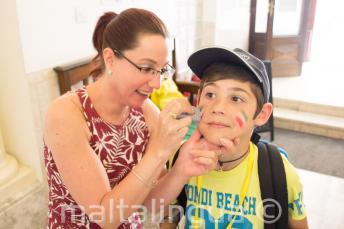 Bir gorevli dil okulu ogrencisinin yuzunu boyuyor