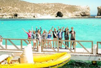Bir grup ogrenci Comino'da Blue Lagoon'un kenarinda el salliyorlar