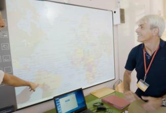 Bir ingilizce ogretmeni interaktif tahtaya bakiyor
