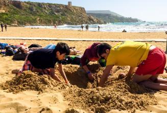 Grup liderleri ve ogrenciler kumsalda bir cukur kaziyor