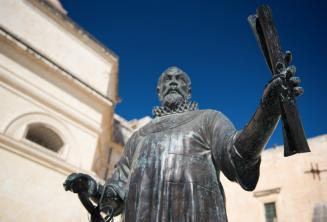 Malta'da bir parşömeni bulunan bir adamın heykeli