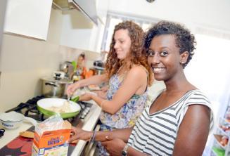 Ev sahibi ailesine yemek hazırlamaya yardım eden bir öğrenci