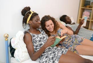 Bir öğrenci ana aile üyesi olan bir kitabı okuyor